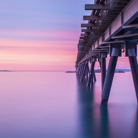 Sunrise long exposure view of the pier leading to the oil workers island in Mussel Shoals, CA.