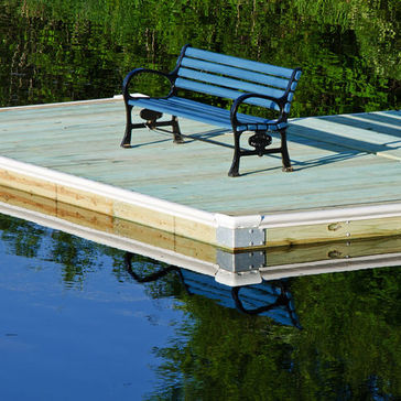 A blue bench on a floating dock on a calm river.