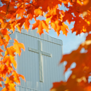 The steeple of a church framed by orange maple leaves.