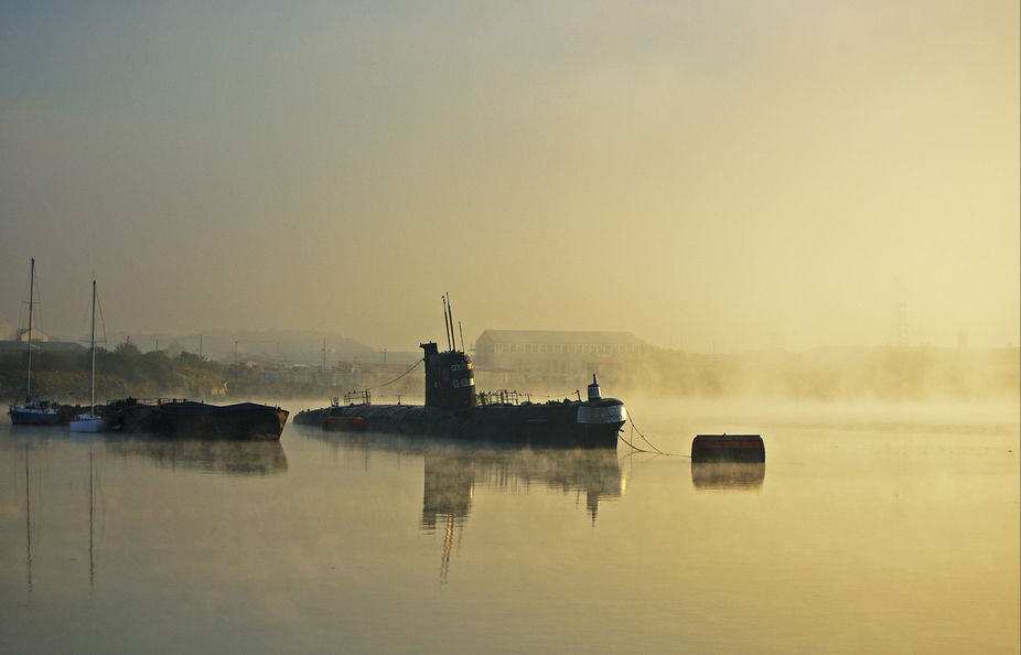 A rusting Foxtrot class Russian submarine sits on the River Medway as the sun rises.