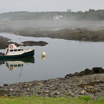 A fishing moored in a calm and foggy cove.