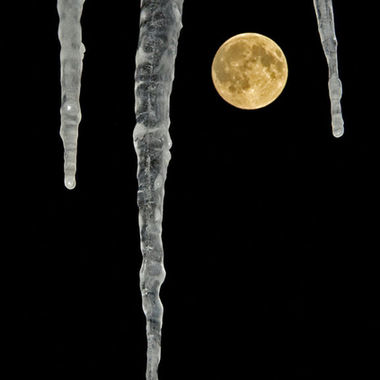 The full moon with three icicles in the foreground.