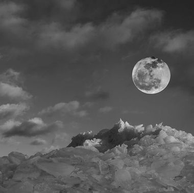 The full moon over a mountain of ice.