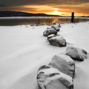 A line of boulders pointing towards the sunrise over the Saint John River on a winter morning.
