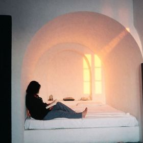 Reading at sunset, in a cave house at Oia, Santorini. The famous Greek sun