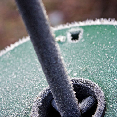 A close-up of a frosty bird feeder pole with squirrel baffle.