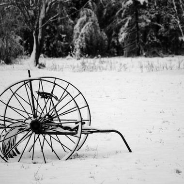 An old piece of farm equipment in a snow covered field.