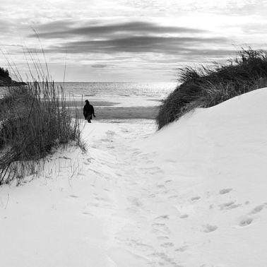 A person walking on the beach in winter.