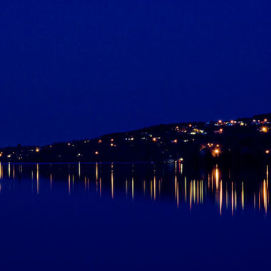 The lights of a small town seen from across a calm river.