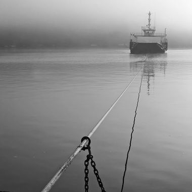 A cable ferry approaching the shore on a calm and foggy morning.