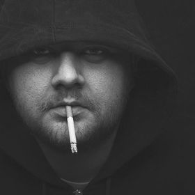 black and white portrait of a man with hood, and cigarette in his mouth
