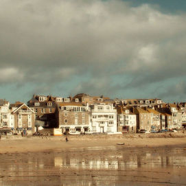 Looking across the harbour at St Ives, Cornwall. A summers day with some fair weather cumulus clouds over the land. The tide is out leaving refle...