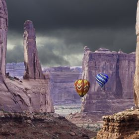 Hot air balloons seek safety below the rim of the canyon as a thunderstorm approaches.