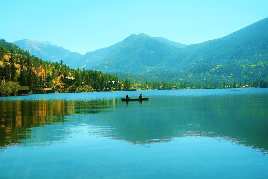 A lone canoe floats peacefully in the middle of Grand Lake carrying 2 fishermen taking in the Tra...
