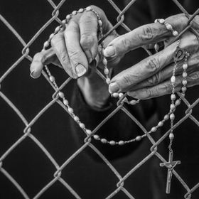 A close up of an old woman's hand holding her rosary through a chain link fence.