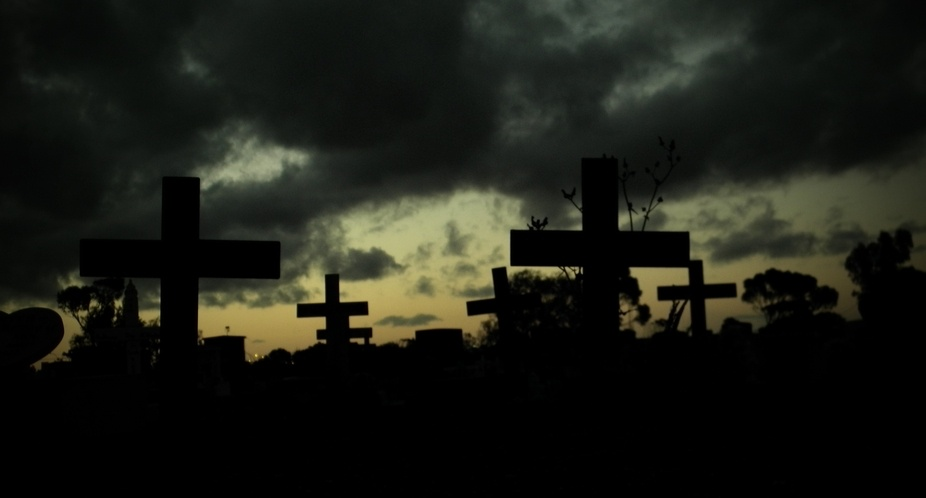 Local cemetery at sunset and the old iron crosses of those departed many decades ago, unmarked gr...