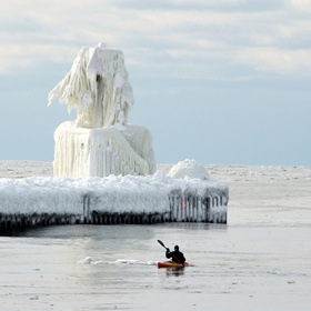 an icy light house is a ice sculpture created by mother nature and enjoyed by a di hard extreme sport kyaker