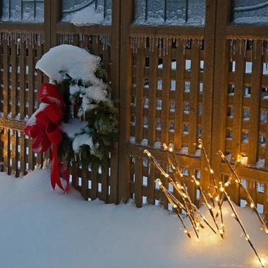 Ice covered lights and wreath on a wooden privacy screen.