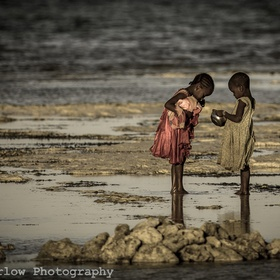 Two girls search for shells on the beach of Nungwi, Zanzibar.