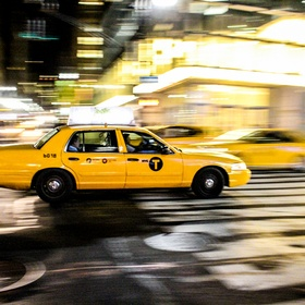 A yellow taxi cab roars through the streets of night time Manhattan