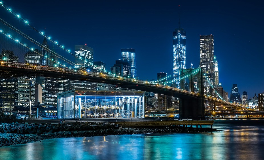 JANE\'S CAROUSEL , BROOKLYN BRIDGE & DOWNTOWN   MANHATTAN ARE ILUMINATED BY THE BEAUTIFUL LIGH...