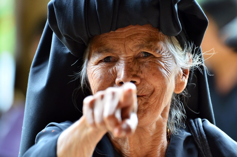 A grandmother who use traditional attire at the ceremony of death, pointing and smiling when goin...