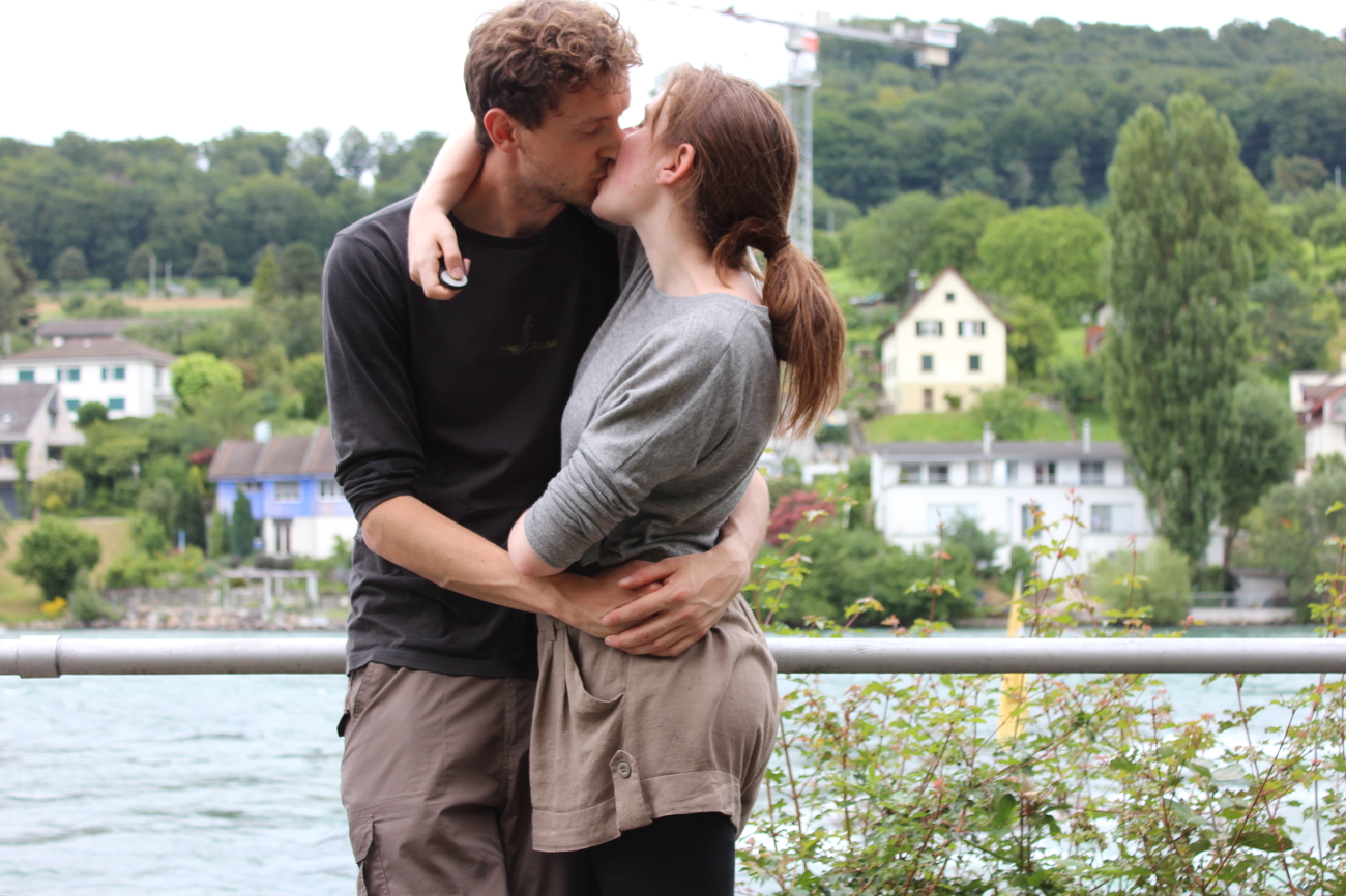 Couple embrace river-side.