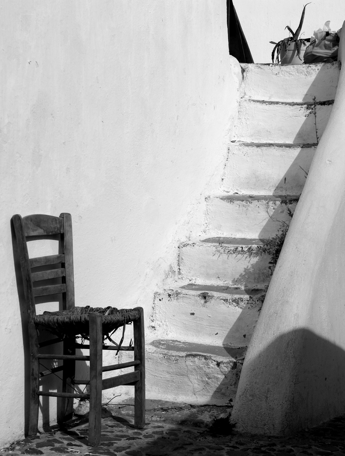 Black & White picture of a lone chair sitting beside stone steps in Oia, Santorini, Greece.