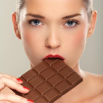 Beautiful women eating chocolate bar
