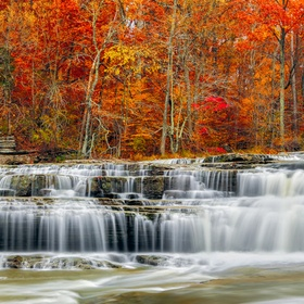Whitewater streams over limestone ledges backed by brilliant, colorful fall foliage at Cataract Falls, a waterfall in rural central Indiana.