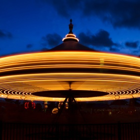 A small merry-go-round spins at twilight on the midway of a carnival.