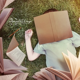 A little boy has fallen asleep on the grass with a brown book on his face. Open books and paper are flying up for an education or story concept.