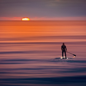 A paddle boarder watching the sunset/sunrise over the distant horizon on the ocean.