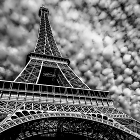 Eiffel Tower with a back drop of splotchy clouds.