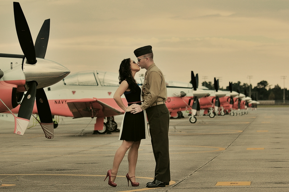 A US Marine and his wife smooching on the military base flight line! :)