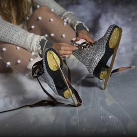 A figure skater laces up skates encrusted with crystals and gold blades.