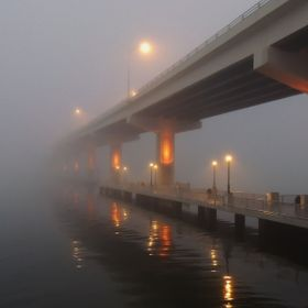 Bridge across River disappearing into fog