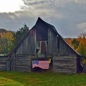 As I photographed this Arkansas barn, a breeze lifted the American flag, bringing the scene to life. I had one shot before all was still again.