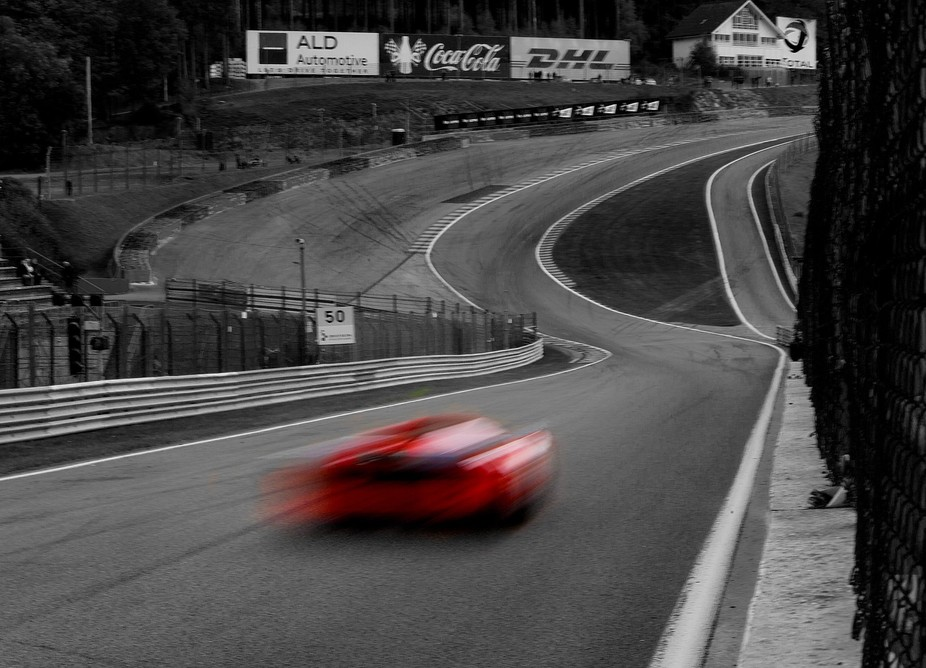 A red ferrari in a black and white world at Spa Francorchamps race circuit