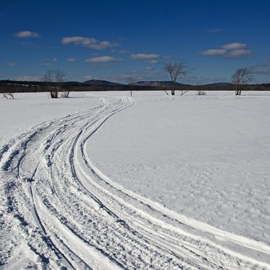 Snowmobile tracks on a frozen river.