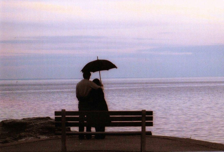During a light rain, two lovers stop to take in the beauty of Long Island Sound.