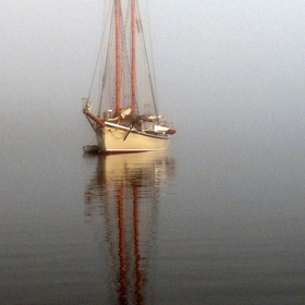 A schooner sits at anchor on a foggy morning in Maine.