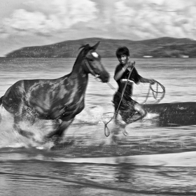 Local village boy exercising his race horse, the early morning Borneo tropical beach that soon to be developed, is good ground for cool exercise.