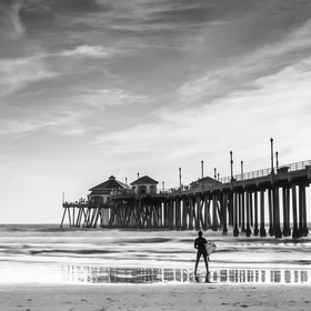 A wide shot of the Huntington Beach Pier with a surfer standing in the foreground.