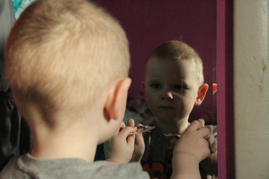 My baby brother likes to look at himself in the mirror.