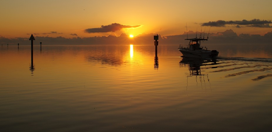 At the sunrise hour, these fishermen head their boat out through this channel to Biscayne Bay, ju...