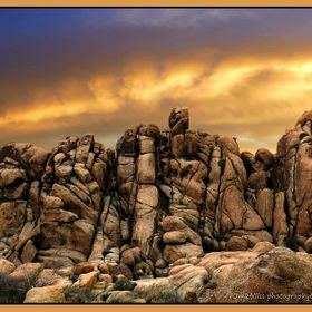 Beautiful monzogranitic boulder formations of Joshua Tree under a sunset sky.