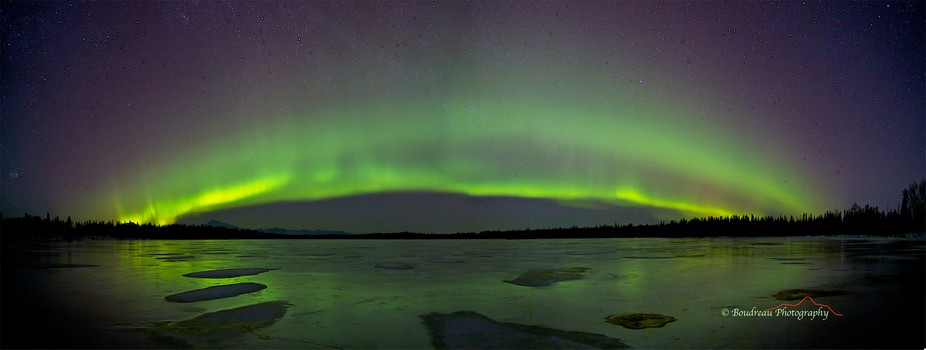 Aurora Borealis traverses over frozen lake in Trapper Creek Alaska
