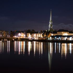 A night time riverside photo of the town of Ayr showing the road bridge and the steeple of the old town hall.