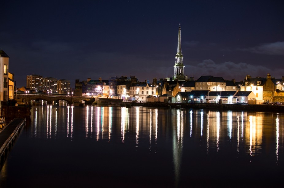 A night time riverside photo of the town of Ayr showing the road bridge and the steeple of the ol...